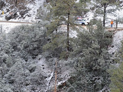 An Arizona Department of Transportation worker and an Arizona Department of Public Safety officer look down the mountain after a passenger car went off the side of Mingus Mountain on Highway 89A, just before noon on Wednesday.<br> Photo courtesy Les Stukenberg/The Daily Courier