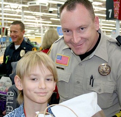 Brandon Minier, 10, of Dewey, waits with Yavapai County Sheriff's Office Deputy Rick Lopez as Brandon's gifts get wrapped, during the Shop with a Cop event Saturday, before heading to Subway inside the Prescott Walmart for lunch.<br> Trib Photo/Sue Tone