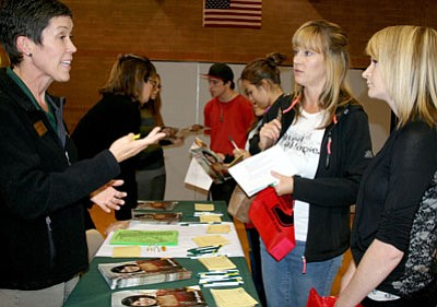 Lisa Mauldin, left, academic advisor with Yavapai College, explains to Kim Peters and daughter, Jennifer Suevers, a senior at Bradshaw Mountain, about the Yavapai College Honors program this past year at BMHS's College Fair.<br> Trib Photo/Sue Tone