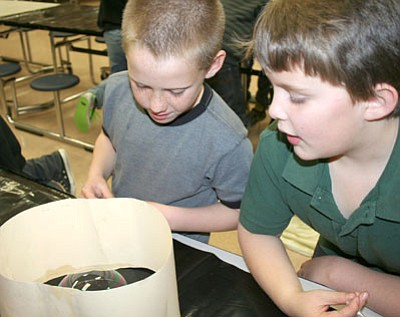 Second-graders Chris Summers, left, and George Salekas create bubbles and learn about surface tension and reflection during their STEAM classes at Mountain View Elementary School this past week.<br> Trib Photo/Sue Tone