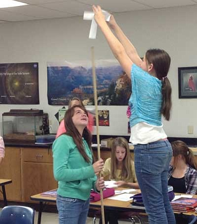 Seventh-graders Amber LaBelle (holding the meter stick) and Hannah Trisdale, right, experiment with a paper helicopter.<br> Courtesy photo