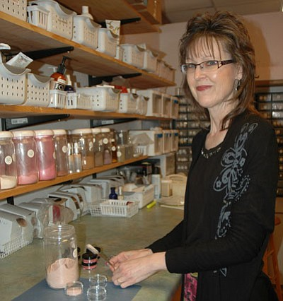 """Owner Marj Melchiors mixes a few samples from the laboratory in the All Natural Cosmetics business in Prescott Valley, situated on Florentine Road. The rows of pure, organic ingredients delight the eye and look great on the skin. Look for Melchiors' own line of """"Earth's Beauty"""" products. The showroom includes hand-made glass jewelry, recycled materials handbags, body products and more.<br> Trib Photo/Briana Lonas"""