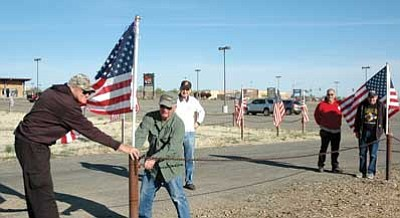 Trib Photo/Cheryl Hartz<BR> Veterans place flags around the Tim's Toyota Center parking lot for the Salute to Heroes event.