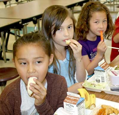Trib Photo/Sue Tone<br> Lake Valley second-graders, from left, Shawnelle Goodluck, Qillian Valencia-Huffman and Tiana Valentin enjoy their selections of fruits and vegetables at lunch table on April 24.