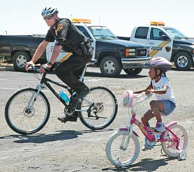 File Photo/Cheryl Hartz<br> Prescott Valley Police bicycle patrol officer Jason Lohman rides with a young participant during a 2012 Bike Rodeo at the Civic Center.
