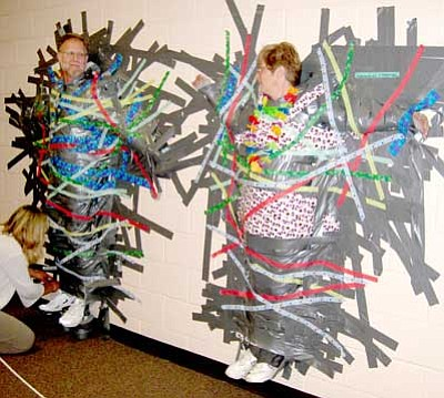 Courtesy Photo<br> Mountain View Elementary reading teacher David Boone, left, and Principal JoAnne Bindell hang by duct tape after students and teachers secured them to the wall.
