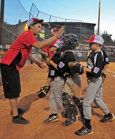 Prescott Valley All-Stars assistant coach Justin King gives high fives to his players as they come in from the field Tuesday night while playing against the Wickenburg All-Stars during the District 10 Little League 9-10 Majors Tournament at Bill Vallely Field in Prescott.<br> Photo courtesy Matt Hinshaw/The Daily Courier