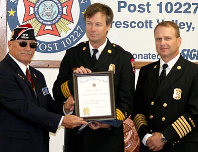 VFW Post 10227 Cmdr. Fred Nelson, left, presents CYFD Asst. Chief Scott Bliss, middle, with the Firefighter of the Year award on Nov. 15 alongside CYFD Chief Scott Freitag.<br> Courtesy Photo