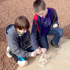 Courtesy Photo<br /><br /><!-- 1upcrlf2 -->Acorn Montessori School seventh-graders Shane Hinds, left, and Harrison Molina get ready to launch a penny in their newly-built catapult Jan. 14 as part of the school's Gifted and Talented Program.