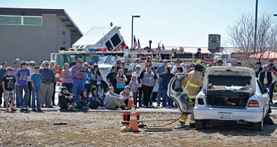 Matt Hinshaw/The Daily Courier<br /><br /><!-- 1upcrlf2 -->People look on as Central Yavapai Fire District Firefighter and EMT Aaron Cobiere Firefighter and Paramedic Gordon Dibble, and Engineer and Paramedic Nick Fournier demonstrate how in an emergency situation they would cut a roof off of a car to gain access to the passengers Saturday March 14 during the Central Yavapai Fire District's 50th Anniversary celebration at the Central Yavapai Regional Training Academy in Prescott Valley.