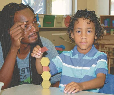 Xavier Lewis stacks blocks shortly before the bell rings in Lani Hammond's kindergarten class at Coyote Springs Elementary School Monday morning as his dad, also Xavier Lewis, sits nearby. (Trib Photos/Sue Tone)