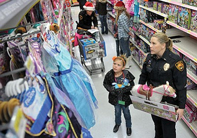 Jeni Robertson, 7, looks at some princess dresses while shopping with Prescott Police Lieutenant Amy Bonnie Saturday morning during the 18th Annual Shop With a Cop event at the Highway 69 Wal-Mart in Prescott.
