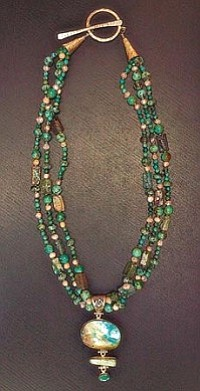 Suzann Trout of Bead Creations creates a necklace with turquoise, recycled old Roman glass and mother of pearl and abalone pendant. Photo by Kim Hoshal.