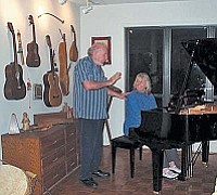 Pollyanna at piano with friend, Jack G., part of her collection of musical instruments on wall.