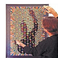 """Paul Gazda stands in front of his artwork Digital Self-Portrait, made of CDs recorded with images of the artist whose shiny surfaces reflect a magnified """"self-portrait"""" of the viewer."""