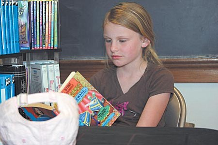 Ilana Ballew, 8-year-old member of the After School Adventure Club in the Jerome Library, was first to arrive for Wednesday's session. She grabbed a book and read until some of her friends showed up. VVN/Philip Wright