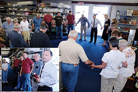 Old Town Mission Executive director Brian Detwiler leads a prayer circle during Wednesday's announcement of the opening of the Old town Mission thrift store May 1