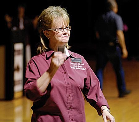 Janice Rollins gives out recognition pins for 25 years of service to the Cottonwood-Oak Creek School District at Friday's assembly.