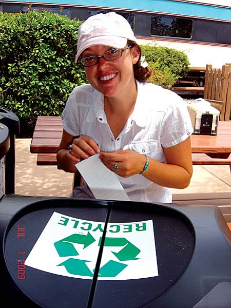 Courtesy Photo Brandi Lee Cooper, a naturalist for the Verde Canyon Railroad, puts labels on the new recycling bins that the company now has on board it scenic train.