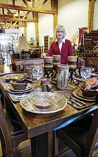 Jane Rolfes stands in front of a dining table and chairs by Jerome's own Western Heritage Furniture – just one of many Western Heritage pieces of custom built furniture carried by Sky Fire.