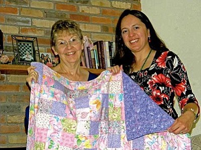 Quilter and cancer survivor Eunice Perschke presents a quilt of pinks and purples to Gina Harris of the Cancer Centers of Northern Arizona Healthcare. The quilt's raffle will raise money in the fight against cancer.