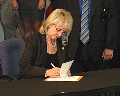 Gov. Jan Brewer signs legislation Friday giving police additional powers to stop and detain suspected illegal immigrants. (Capitol Media Services photo by Howard Fischer)
