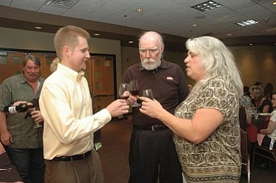 Eric Glenn of the UofA Agricultural Extension Service, toasts with Tom Pitts, chairman of the Verde Valley Wine Consortium, and Paula Woolsey, education committee chairman for the consortium, to the continued success of the consortium.