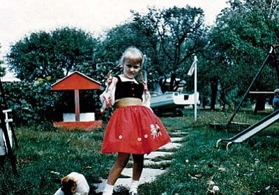 "Dottie Presmyk at age 5 in 1960 in the back yard of the home she lived in until she was a teenger in Findlay, Ohio. ""I'm sure it is one of the few boughten dresses I had,"" she says. "" Mom made us five new dresses every school year to start new."" Submitted by Dottie Presmyk of Camp Verde."