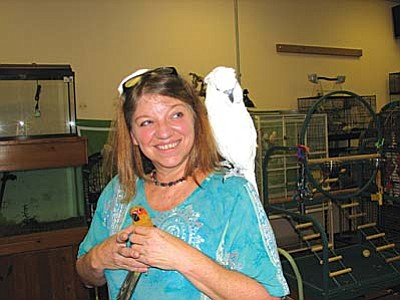 "Village resident Roxanne James manages Village Pet Supply in the Outlet Mall. Her business is called ""Birds Fly Free"" because she carefully trims their wings so they can glide to soft landings but remain unable to fly off into danger. If you purchase one of her birds, she offers unlimited free trimming because she enjoys keeping in touch with the birds and their new people friends."