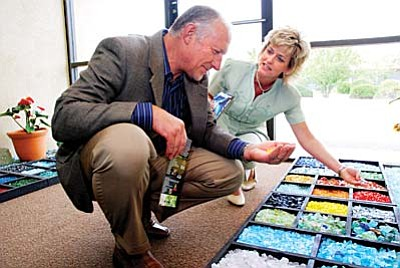 Sunwest Bank employees Andy Phillips and Lori Simmons examine glass beads on display at Garden of Glass on Cherry Street in Cottonwood.