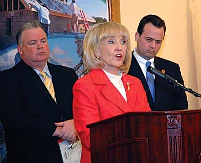 Flanked by state commerce chief Don Cardon and House Speaker Kirk Adams, Gov. Jan Brewer on Monday explains a package of tax cuts she believes will lure businesses to Arizona. (Capitol Media Services photo by Howard Fischer)