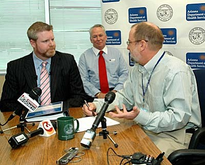State Health Director Will Humble, right, explains to attorney Ryan Hurley why he is refusing to accept an application by a group of doctors to operate a medical marijuana dispensary in Scottsdale. Dr. Joel Colley, medical director of the proposed dispensary, listens in.  (Capitol Media Services photo by Howard Fischer)