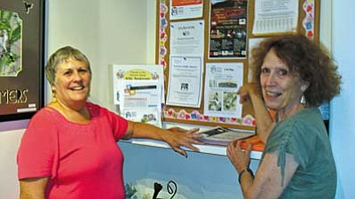 Library volunteers Diane Schwilling (pictured left) and Valerie Girard, discuss the bulletin board display at SPL-V.