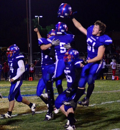 Camp Verde's David Stanley leaps and hoists his helmet in celebration after Camp Verde's 41-31 win over Mingus Union High School Friday night. VVN/Sean Morris