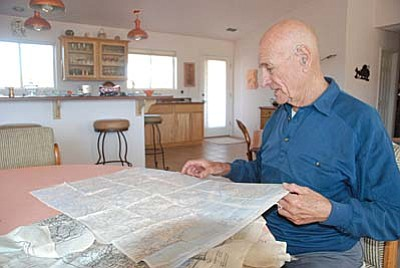 Camp Verde resident Dick Schmidt displays the collection of maps he was issued during the war. Although nicely printed on cloth he says they were not very accurate.