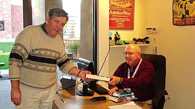 Bruce Vegter, SPL-V volunteer, checks out a library book for William Raleigh. Mr. Raleigh likes to the convenience of driving his golf cart to the library.