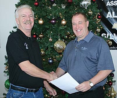 Larry Green Chevrolet general manager Graham Robertson, right, hands Kit Amolsch a check to cover the cost of buying turkeys for the Seniors Dinner at the Verde Valley Moose Lodge 1440 in Clarkdale on Dec. 11. VVN/Philip Wright<br /><br /><!-- 1upcrlf2 -->
