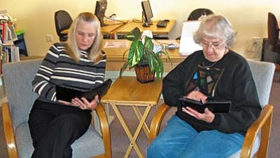 Cheryl Yeatts (left), manager of SPL-V,  and Dotte VandeLinde right), former manager of SPL-V, take a few quiet moments to enjoy their e-readers.