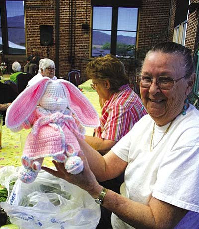 Joyce Johnson shows off one of the bunnies she is famous for creating among the Creative Friends group. Behind her are Rose Marie Delfs and Dana Best.