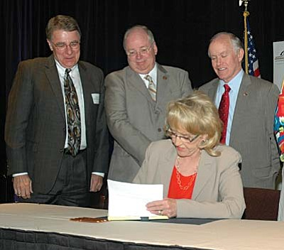 Gov. Jan Brewer signs legislation Friday with a package of tax cuts for business she said will stimulate the economy. Looking on are Sen. Steve Yarbrough, House Speaker Andy Tobin and Senate President Steve Pierce.  (Capitol Media Services photo by Howard Fischer)