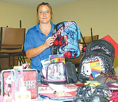 Heather Lessert of the Old Town Mission shows some of the school supplies needed to fill more than 800 backpacks for students in the Verde Valley, Sedona and Northern Arizona. The annual Back to School Backpack program is one of the Old Town Mission's most popular community service events.
