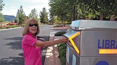 Library patron Estel Menor returns library books to the book drop boxes at Sedona Public Library in the Village.