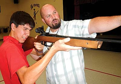 American Heritage Academy has selected American Heritage Academy's Athletic Director/Shooting Sports Coordinator, Aaron Anderson, as its Educator of the Year. Here, Anderson works with student Joshua Saver on his rifle skills.