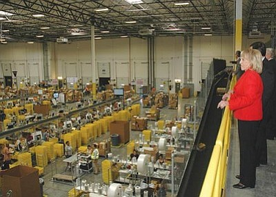Gov. Jan Brewer touring an Amazon warehouse in Phoenix last year, before the state levied its assessment on the company. (Capitol Media Services file photo by Howard Fischer)<br /><br /><!-- 1upcrlf2 -->