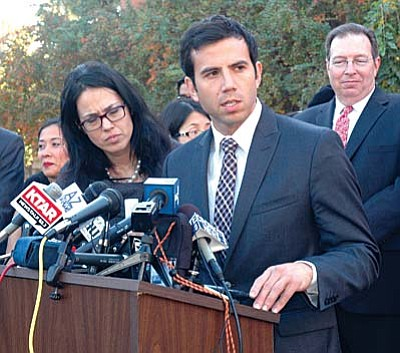 Nicholas Espiritu, an attorney with the Mexican American Legal Defense and Educational Fund, explains a lawsuit filed Thursday challenging the order issued by Gov. Jan Brewer denying state driver licenses to thousands of illegal immigrants who qualify for the federal ``deferred action' program which allows them to remain legally and work in this country.  The American Civil Liberties Union, headed in Arizona by Alessandra Soler, left, also is part of the lawsuit. (Capitol Media Services photo by Howard Fischer)