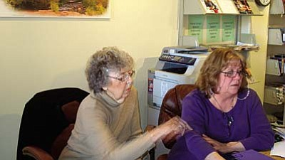Library volunteer Gayle Macklin shows Marybeth Carlile how to download library books to her NOOK.