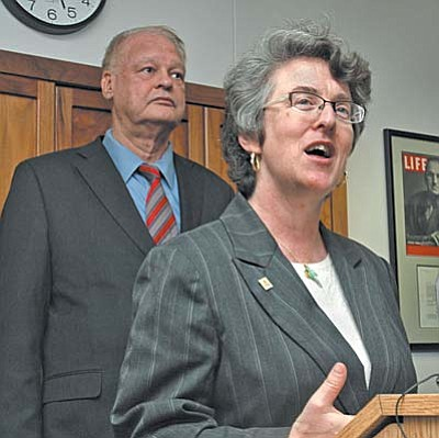 Jennifer Pizer, an attorney with Lambda Legal, and Attorney General Tom Horne detail the agreement Monday they reached an agreement over what cities can -- and cannot -- approve in ordinances granting rights to domestic partners. (Capitol Media Services photo by Howard Fischer)