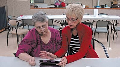Vickie LaFrance (pictured right) shows Sandra Leaverton how to download free library books to her e-reader.  The Library recently offered an e-reader workshop for residents of Sedona Winds.