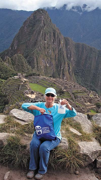 Cheryl displays book bag and water bottle at Machu Picchu.