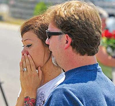 Juliann Ashcraft, wife of Granite Mountain Hotshot Andrew Ashcraft, is consoled Monday by her father-in-law, Tom Ashcraft, at the memorial outside of Prescott Fire Department Station No. 7, where the Granite Mountain Hotshots are based. Nineteen hotshots perished in the Yarnell Hill fire Sunday night. Matt Hinshaw/The Daily Courier